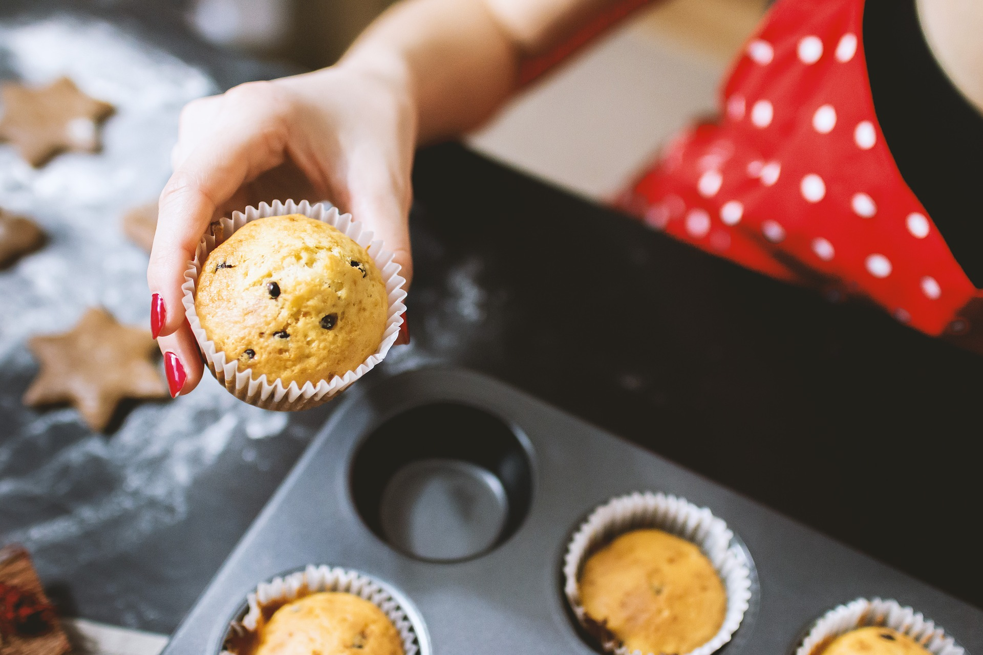 Woman holding up a muffin with baking pan full of other muffins | The Refinery